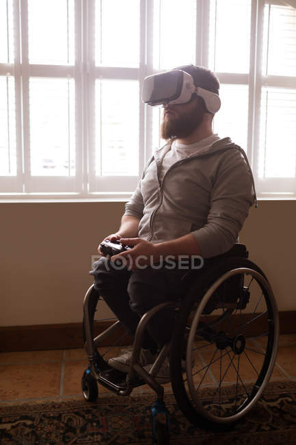 Disabled man using virtual reality headset at home — Stock Photo