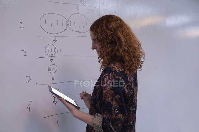 Female executive using digital tablet near whiteboard in office — Stock Photo
