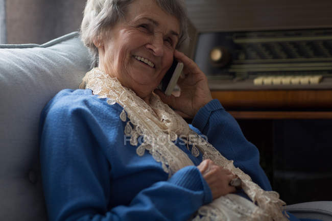 Senior woman talking on mobile phone at home — Stock Photo