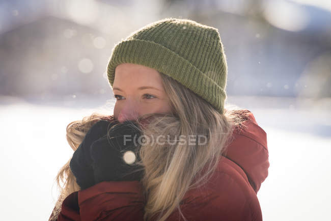 Primo piano di donna in abbigliamento invernale in piedi sul paesaggio innevato — Foto stock