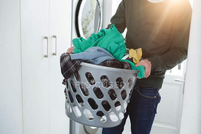 Man holding basket of laundry clothes at home — Stock Photo