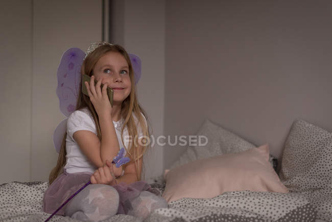 Girl talking on mobile phone in bedroom at home — Stock Photo