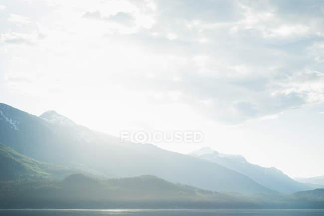 Montañas con nubes blancas en un día soleado - foto de stock