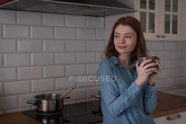 Thoughtful woman standing with cup of coffee in kitchen — Stock Photo