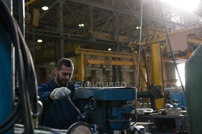 Attentive technician in protective workwear working in metal industry — Stock Photo
