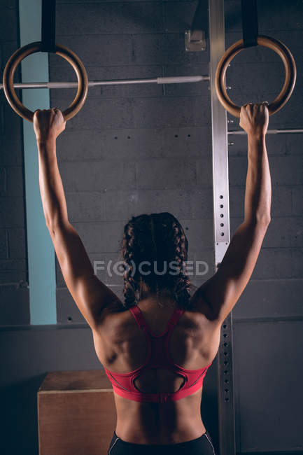 Rear view of fit woman exercising with gymnastic rings in the gym — Stock Photo