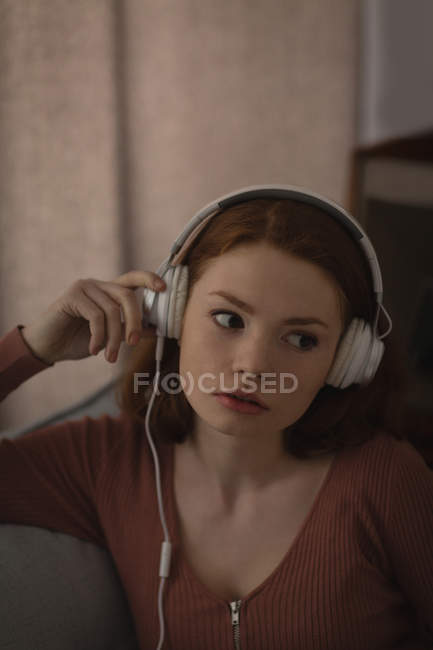 Woman listening music on headphones at home — Stock Photo
