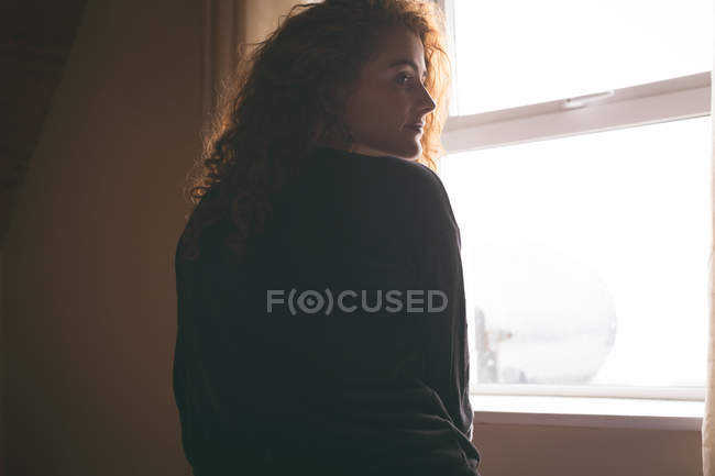Rear view of thoughtful woman standing near window at home — Stock Photo