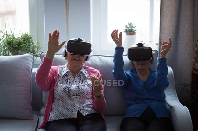 Amigos mayores que usan auriculares de realidad virtual en casa - foto de stock
