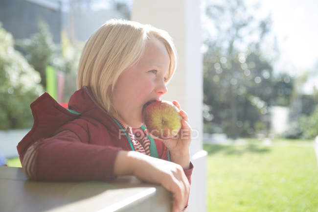 Boy eating apple in the porch on a sunny day — Stock Photo