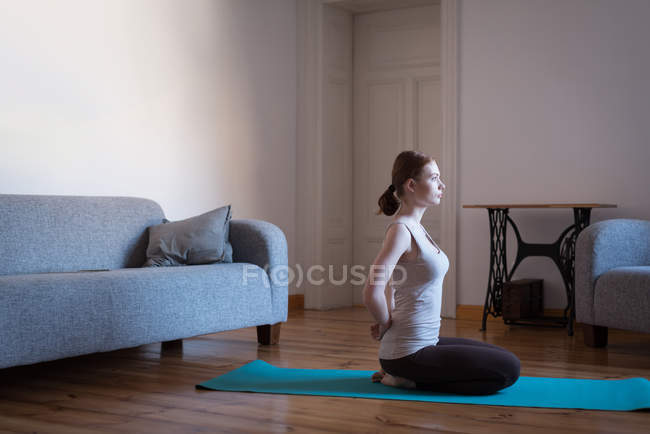 Young woman practicing yoga in the living room at home — Stock Photo