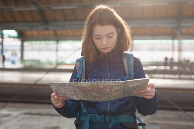 Female traveler with backpack looking at map while waiting for train — Foto stock