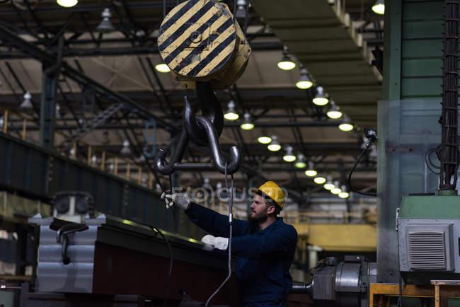 Attentive technician adjusting metal equipment in hook — Stock Photo