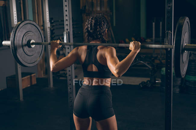 Rear view of fit woman lifting the barbell in the gym — Stock Photo
