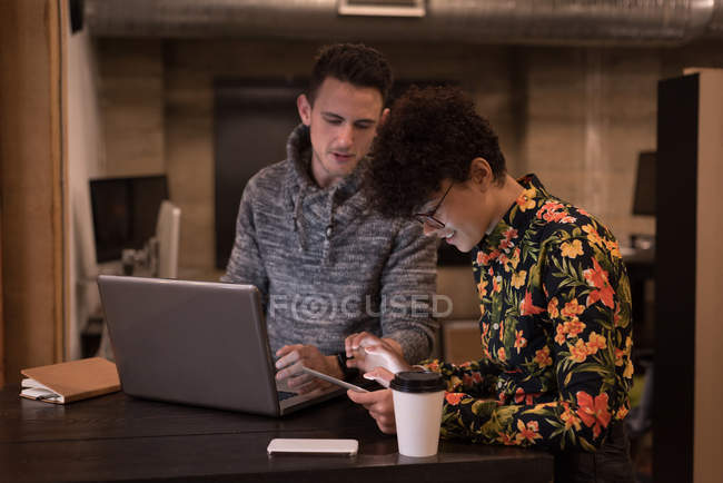 Male and female executive discussing over digital tablet in office — Stock Photo
