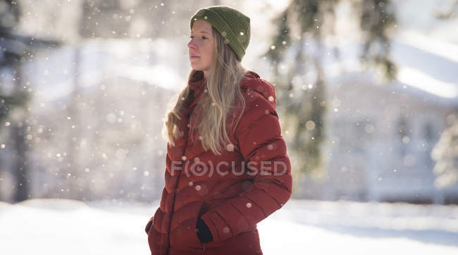 Thoughtful woman standing on snow covered landscape during winter — Stock Photo