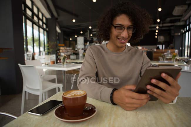 Homme heureux en utilisant une tablette numérique au restaurant — Photo de stock
