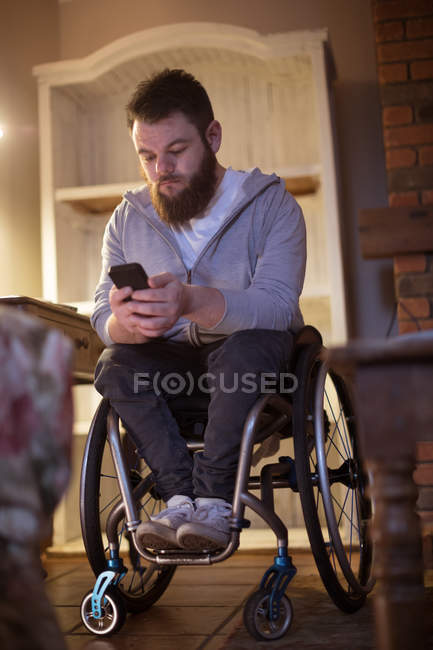 Disabled man using mobile phone at home — Stock Photo