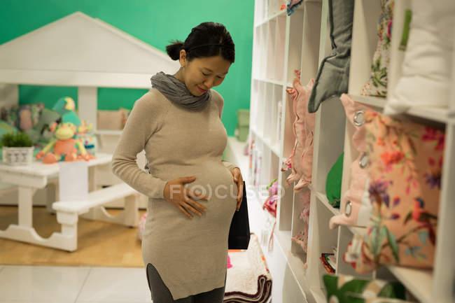 Счастливая беременная женщина прикасается к животу во время покупок — стоковое фото