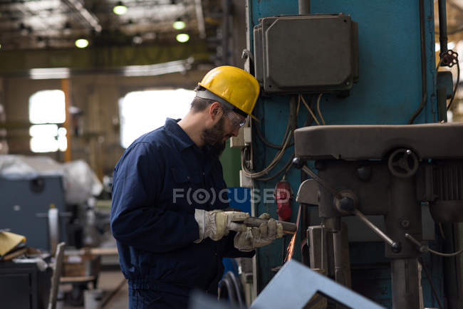 Technician in protective workwear cutting metal in industry — Stock Photo