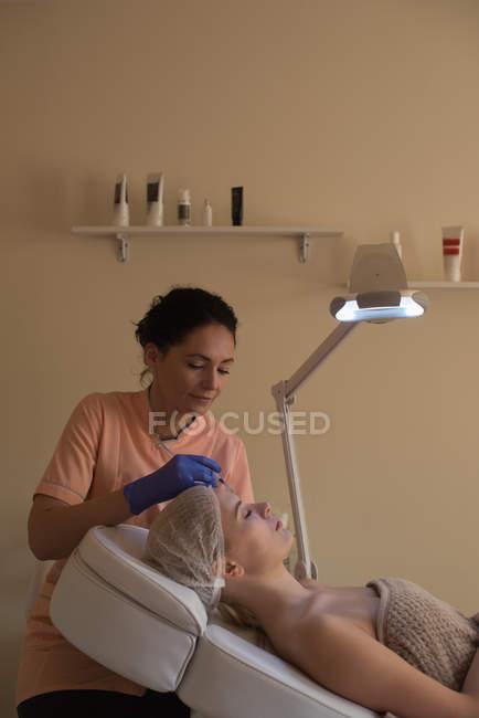 Estetista dando trattamento di bellezza al cliente femminile in salotto — Foto stock