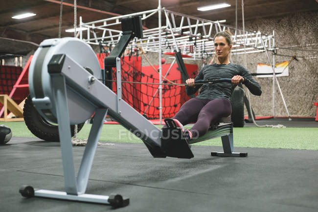 Muscular woman exercising on rowing machine at gym — Stock Photo