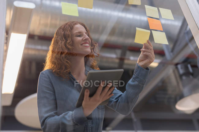 Female executive using digital tablet while reading sticky notes in office — Stock Photo
