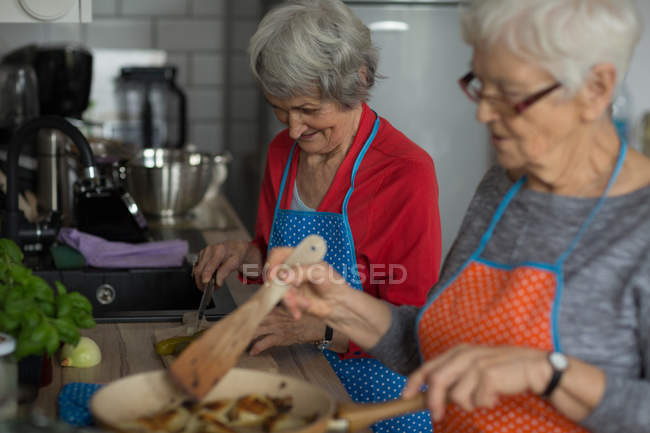 Senior friends cooking food together in kitchen at home — Stock Photo