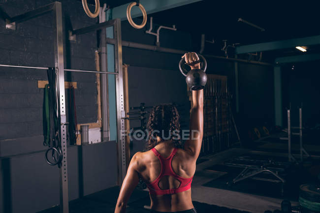 Rear view of fit woman exercising with kettlebell in the gym — Stock Photo