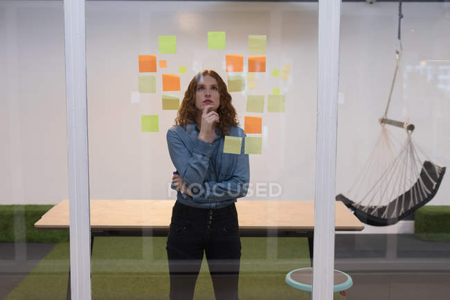 Thoughtful female executive reading sticky notes on glass in office — Stock Photo
