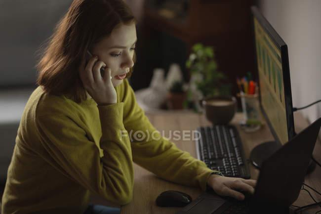 Femme parlant sur un téléphone mobile tout en utilisant un ordinateur portable à la maison — Photo de stock