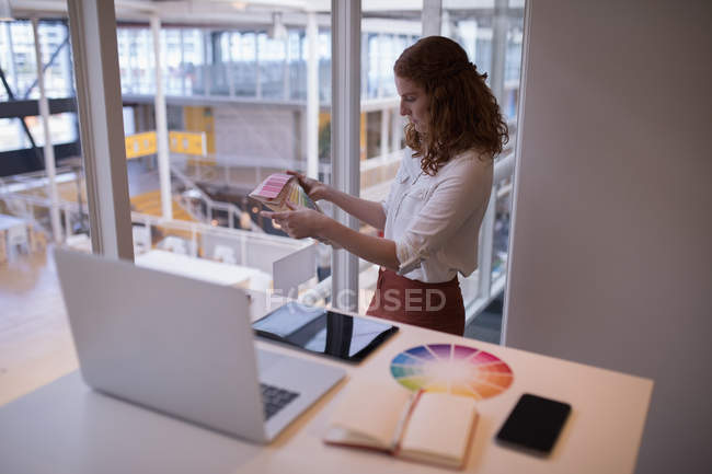 Female graphic designer looking at color swatch book in office — Stock Photo