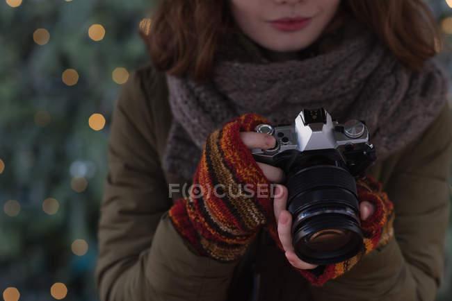 Seção média de mulher em roupas de inverno segurando câmera vintage — Fotografia de Stock