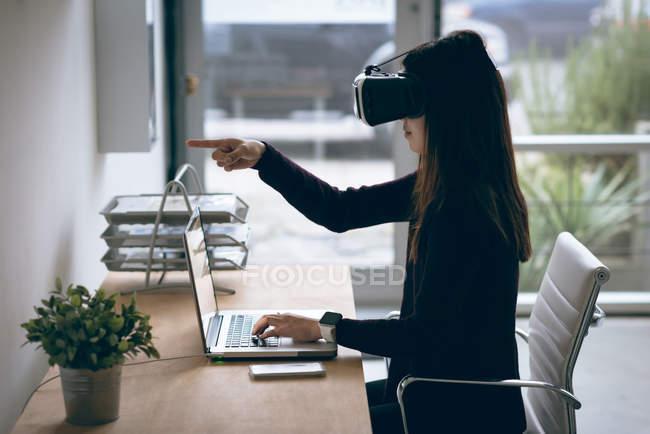 Executive working on laptop while using virtual reality headset in office — Stock Photo