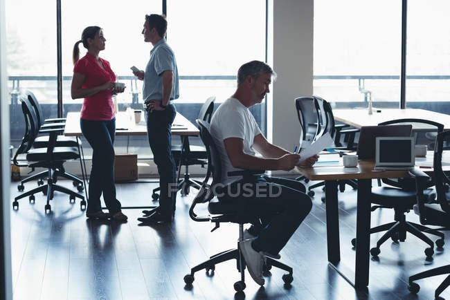 Бізнесмен, дивлячись на документі колег, які взаємодіють один з одним в офісі — стокове фото