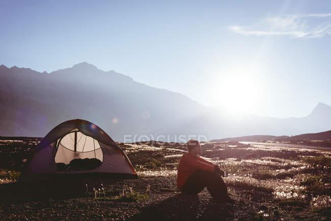 Nachdenklicher Mann sitzt an einem sonnigen Tag in Zeltnähe — Stockfoto