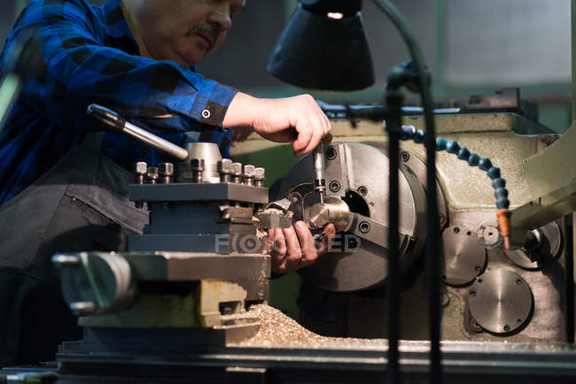 Technician in protective work wear repairing metal in industry — Stock Photo