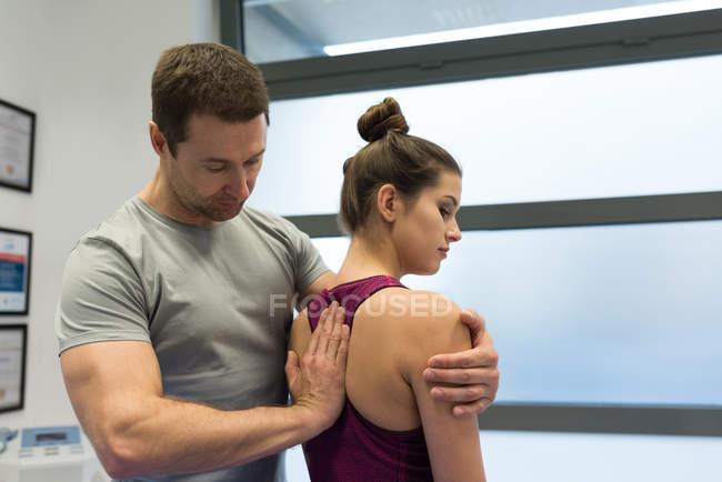 Fisioterapista restituendo massaggio alla donna in clinica — Foto stock