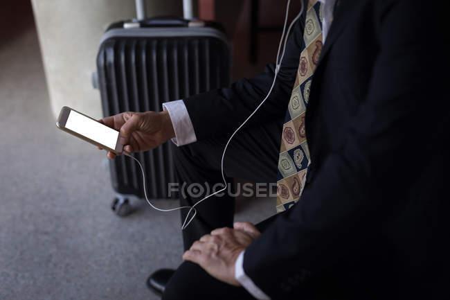 Sección media del hombre de negocios usando un teléfono inteligente en la habitación de hotel - foto de stock