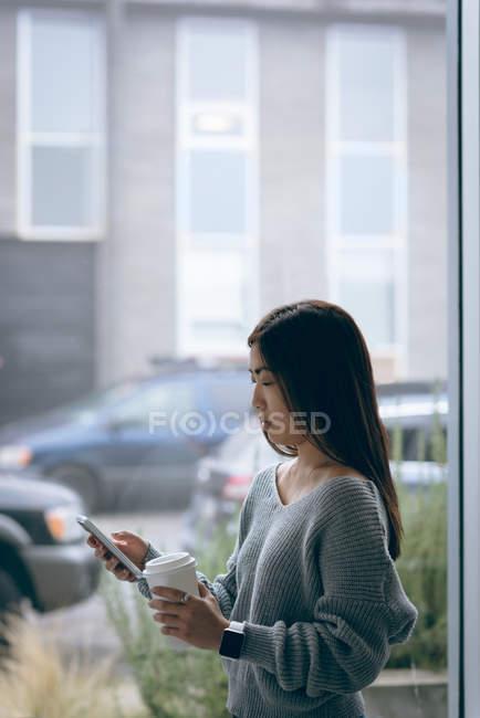 Исполнительный, с помощью мобильного телефона имея кофе в офис — стоковое фото