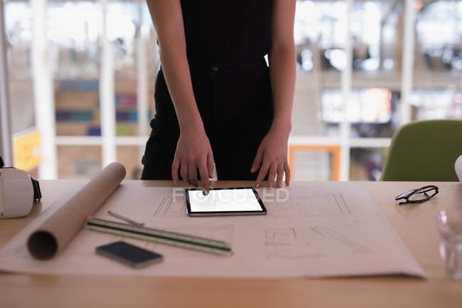 Metà di sezione di progettista grafico femminile using digital tablet in ufficio — Foto stock