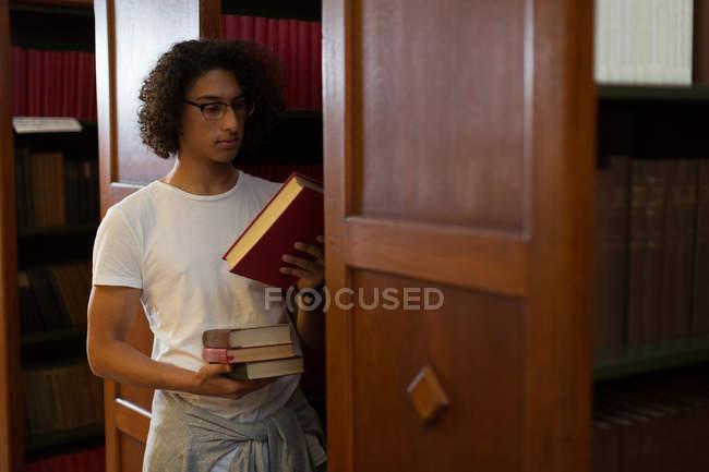 Uomo selezionando un libro da scaffale per libri in libreria — Foto stock