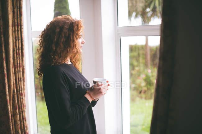 Donna premurosa che guarda attraverso la finestra mentre prende una tazza di caffè a casa — Foto stock
