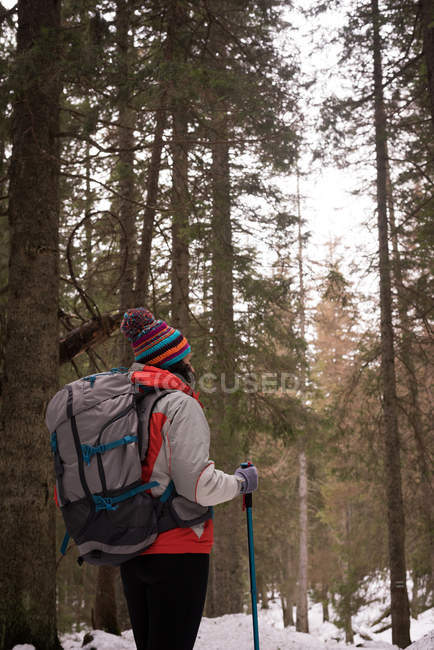 Thoughtful woman with backpack and hiking pole in forest — Stock Photo