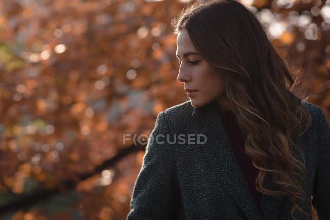Задумчивая женщина в парке в солнечный день — стоковое фото