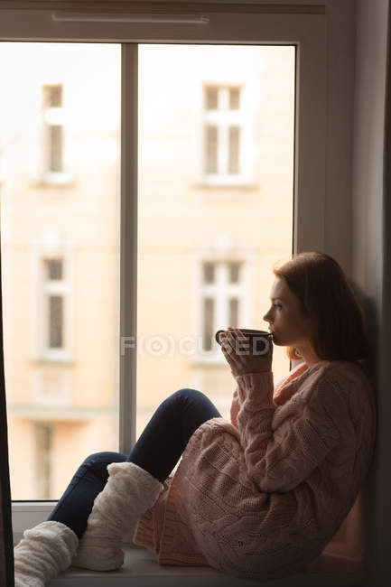 Woman having coffee while looking through window at home — Stock Photo