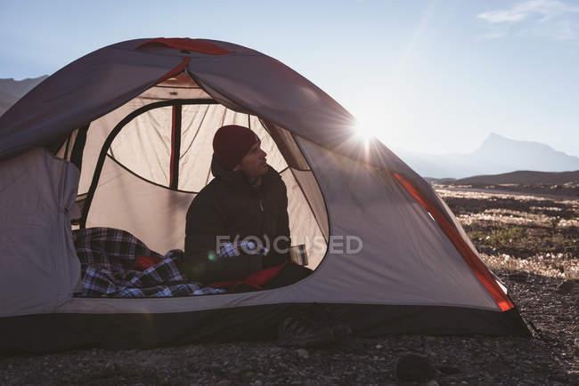 Homem atencioso relaxando na tenda em um dia ensolarado — Fotografia de Stock