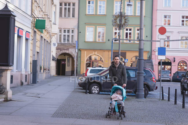 Father walking with his daughter on sidewalk in city street — Stock Photo