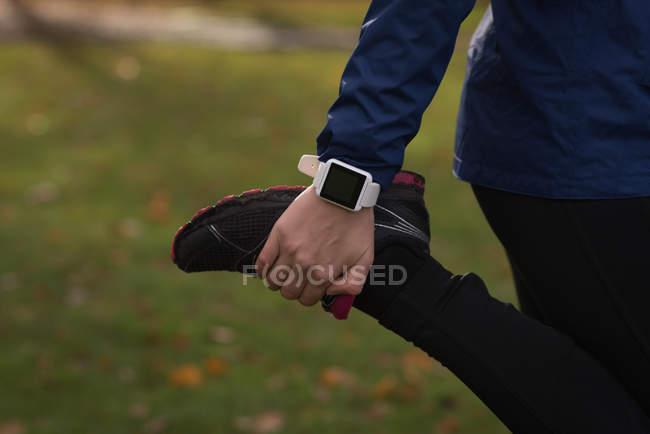 Section médiane de femme effectuant exercice d'étirement dans le parc — Photo de stock