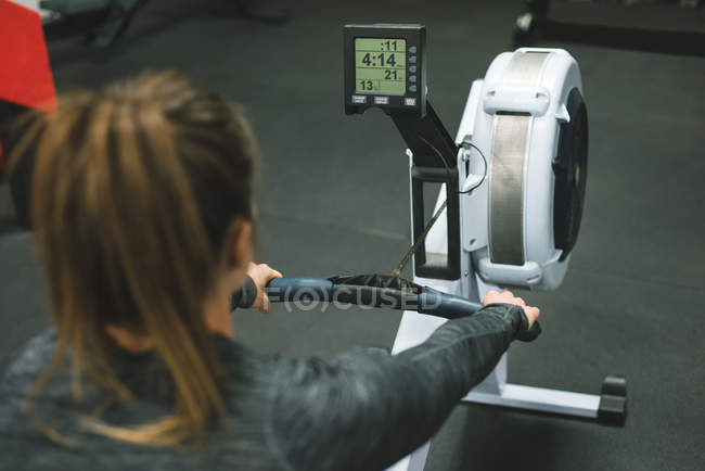 Rear view of muscular woman exercising on rowing machine at gym — Stock Photo